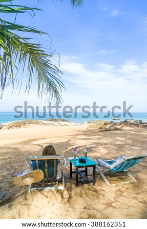 Woman on a sun lounger on a tropical beach with hat