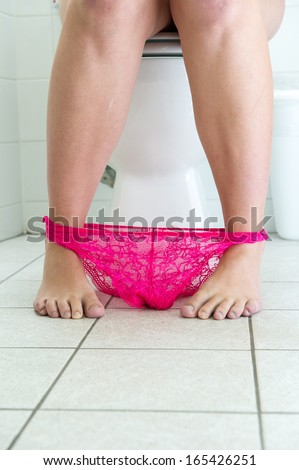 woman on a toilet with her pink lace panties at her feet.   - stock photo