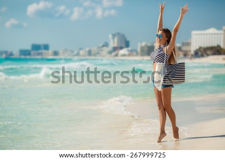 Woman on a tropical beach with beach bag. fit young woman with stripy bag at tropical beach. beautiful girl walking the summer beach - stock photo