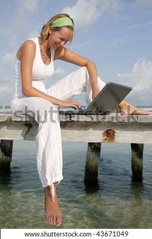 Woman on a tropical jetty with a laptop - stock photo