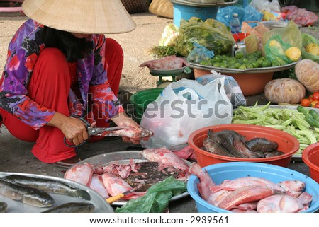 Woman on a vietnamese market preparing the freshly caught fish