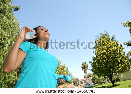 Woman on a walk with water and dumbbells - stock photo