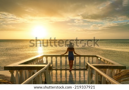 Woman on balcony looking at the beautiful sunset - stock photo