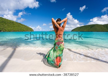 woman on beach with starfish and tropical colorful sarong - stock photo