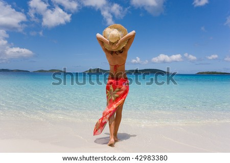woman on beach with tropical sarong and hat in virgin islands