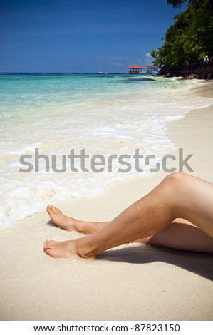 Woman on beautiful tropical beach with bright sand - stock photo