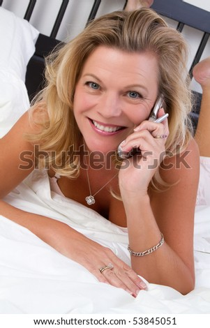 Woman on bed talking on phone - stock photo