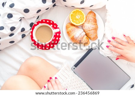 Woman on bed with tablet, breakfast and coffee, relaxing on a sunday morning - stock photo