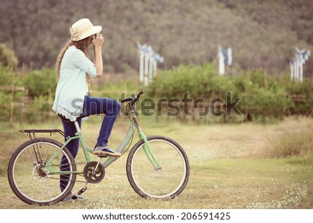 Woman on bicycle taking photo with wind turbine in background