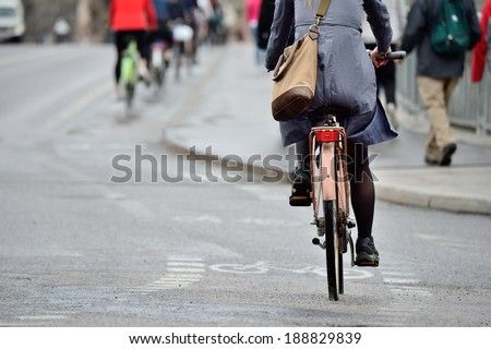 Woman on bike in light rain on her way home from work - stock photo