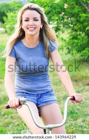 Woman on bike outdoors smiling - stock photo