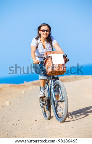 Woman on bike outdoors smiling. Vertical view - stock photo