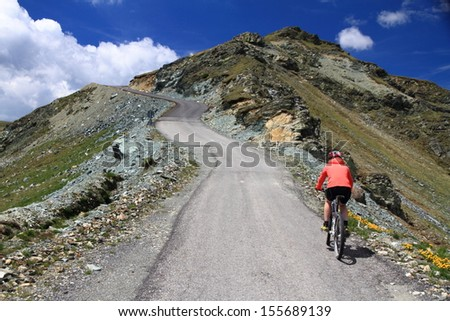 Woman on bike riding a mountain road