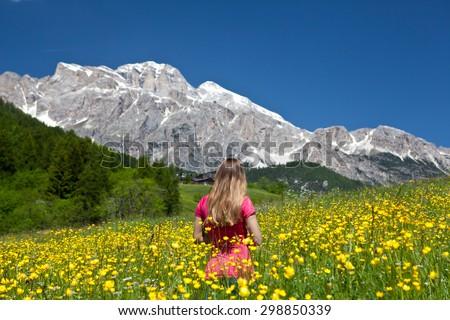Woman on blossom field - Dolomiti mountains - Italy - stock photo