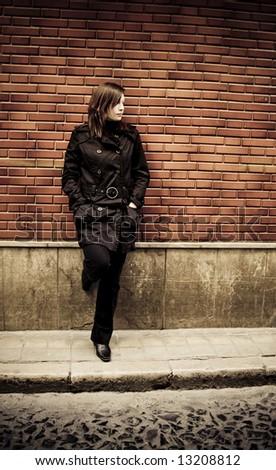 Woman on brickwall, dark urban toned. - stock photo