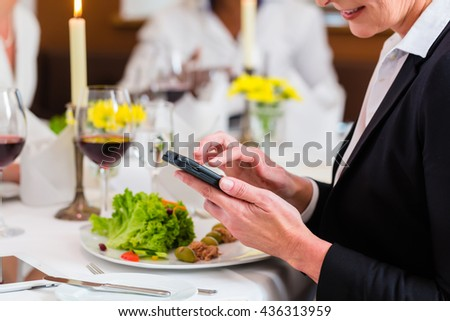 Woman on business lunch in restaurant checking mails on phone