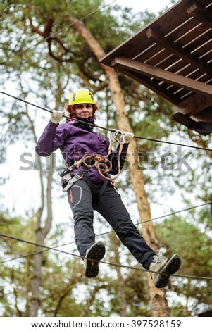 Woman on cables in an adventure park on a difficult course - stock photo
