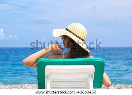 woman on chaise longue at the beautiful beach . - stock photo