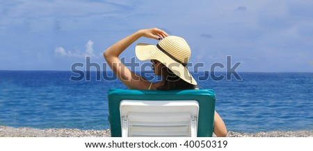 woman on chaise longue at the beautiful beach . Lots of copy space. - stock photo