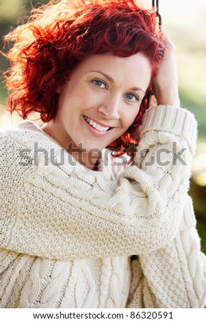 Woman on country garden swing - stock photo