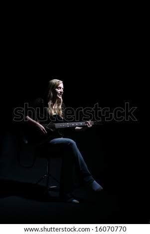 woman on dark stage performing with the guitar - stock photo