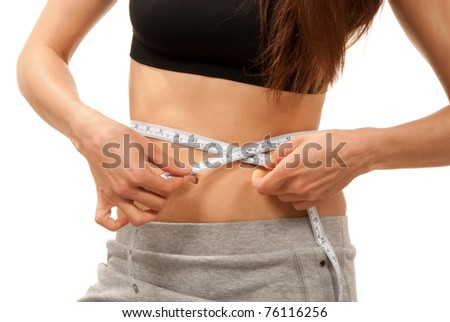 Woman on diet try to waight loss control measuring her waist with white tape measure on a white background - stock photo