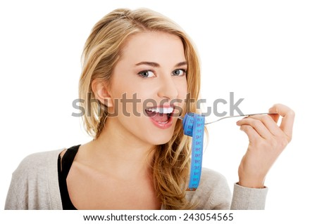 Woman on diet with tape-measure on fork - stock photo