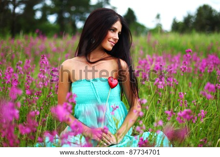 woman on flower field heart in hands - stock photo