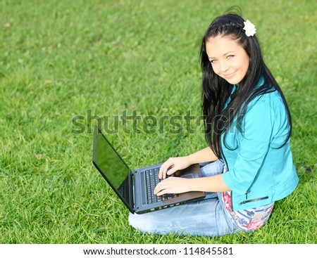 woman on grass with laptop in summer park - stock photo