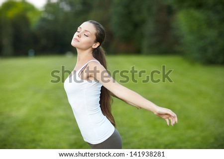 woman on green grass field feel freedom - stock photo