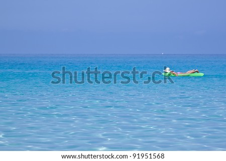 Woman on green mat in sea on vacation