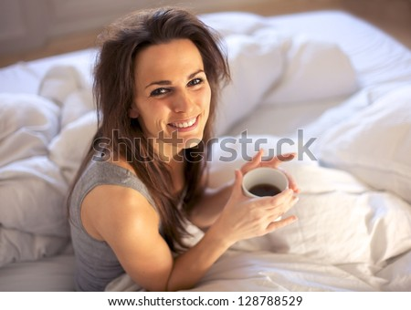 Woman on her bed smiling while holding a cup of coffee - stock photo
