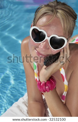 Woman on her phone in the summer sun - stock photo