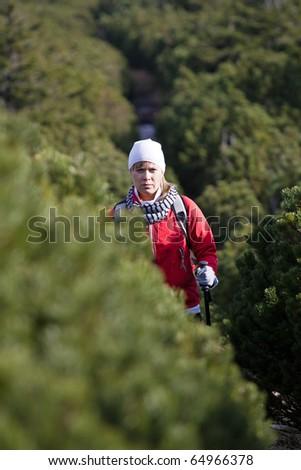 Woman on hiking trail, Nordic Walking in Autumn mountains - stock photo
