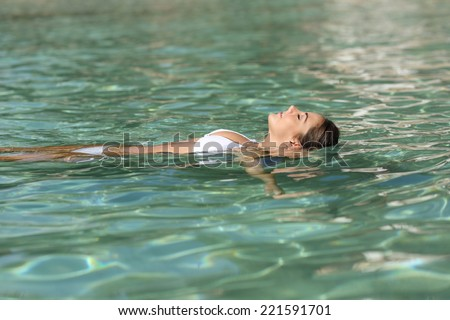Woman on holidays relaxing and bathing in a tropical beach with turquoise water - stock photo
