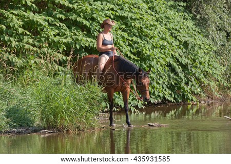 Woman on horse in the water - stock photo