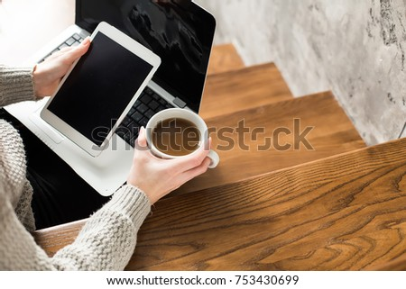 Woman on house stairs relaxing, reading email on mobile wifi connection