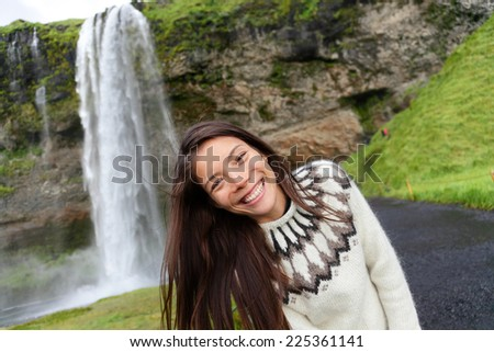 Woman on Iceland in Icelandic sweater by waterfall outdoor fun. Candid beautiful female model in nature landscape with tourist attraction Seljalandsfoss waterfall on Ring Road. - stock photo