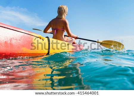 Woman on kayak in ocean with blue sky background - stock photo