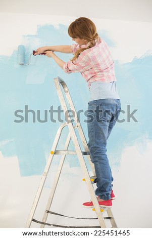Woman on ladder painting wall with paint roller - stock photo