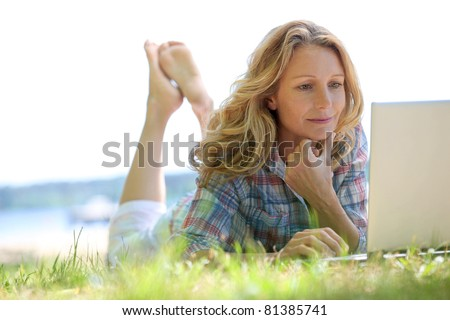 Woman on laptop outside - stock photo