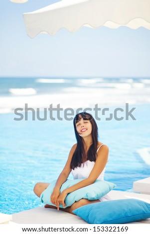 woman on lounger near swimming pool - stock photo