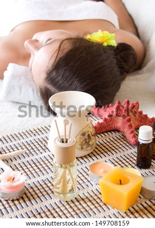 Woman on massage table with oils, essential oils, candles, scents.