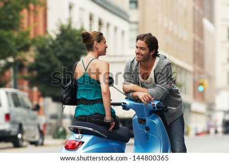 Woman on moped talking to man in street - stock photo