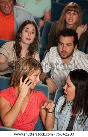 Woman on phone annoys audience in theater - stock photo