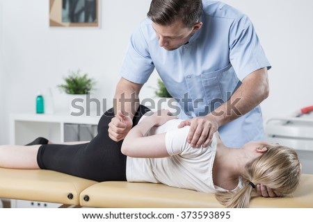 Woman on physiotherapy table lying on the side - stock photo