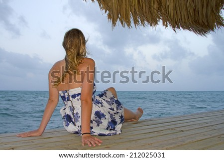 Woman on pier looking out at ocean - stock photo