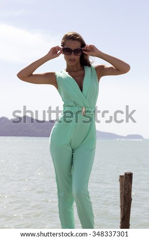 Woman on pier of boat station in black sunglasses and stylish elegant clothes poses enjoying amazing view. Fashion look. Phuket island, Thailand - stock photo