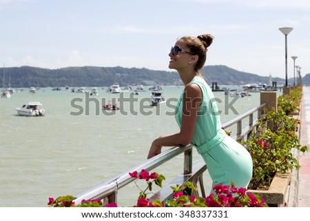 Woman on pier of boat station with hair up in black sunglasses and stylish elegant clothes poses enjoying amazing view. Fashion look. Phuket island, Thailand - stock photo