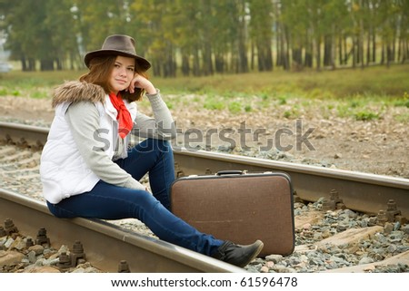 Woman on  railway sitting with her suitcase - stock photo
